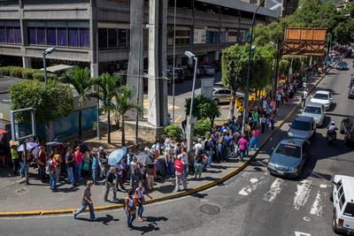 """CARACAS (VENEZUELA).- Fotografía del, de un grupo de personas haciendo fila para entrar en un supermercado en Caracas (Venezuela). """"Más barato imposible"""" repite a viva voz una caraqueña que vende harinas en el mercado de Petare, la favela más grande de Latinoamérica, donde cientos de comerciantes ofrecen productos básicos, generalmente escasos en la nación caribeña, a precios 20 veces más caros que los establecidos por el Gobierno. EFE"""