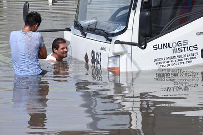 Un hombre baja de su unidad para verificar el estado en que se encuentra, luego de quedar varado en el Periférico de Torreón.