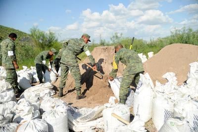 Soldados llenan costales de arena.