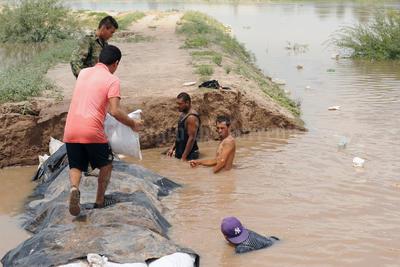 Los habitantes de Hormiguero se sumergían en el agua para colocar los costales llenos de arena.