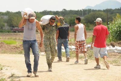 En el ejido Hormiguero los habitantes con ayuda del Ajército reforzaban la seguridad con costales.