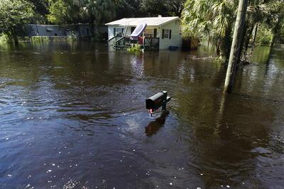 Pasco , Florida.- Un buzón de correo y una casa se ven inundadas en la zona Elfers Parkway del condado de Pasco, Florida. Por el desbordamiento del río Anclote, en Elfers  Fla. El río Anclote al noroeste de Tampa se prevé que un importante nivel de inundación. Los gestores de emergencias emitieron evacuaciones obligatorias para algunos parques móviles, casas y edificios de apartamentos . (AP)