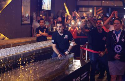 Dubai, Emiratos Árabes Unidos.- Ahmad Taher, gerente de alimentos y bebidas  de Citymax hoteles en Dubai, Emiratos Árabes Unidos, empuja sobre un vidrio en un exitoso tiro de caída de dominó más largo del mundo disparado. El hotel Huddle Sports Bar & Grille en Bur Dubai rompió el récord mundial con más de 6.000 vasos de bebida energética y tragos de whisky bajo la supervisión de un observador del libro Guinness de los Récords . (Foto AP)