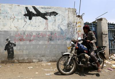 SANÁ (YEMEN).- Un motorista yemení pasa delante de un grafiti protesta contra las operaciones con drones por parte de Estados Unidos en el Yemen, en Saná. Al menos seis supuestos integrantes de Al Qaeda fallecieron hoy en una nueva tanda de ataques con drones de EEUU sobre la provincia de Marib, Yemen, según medios locales. EFE