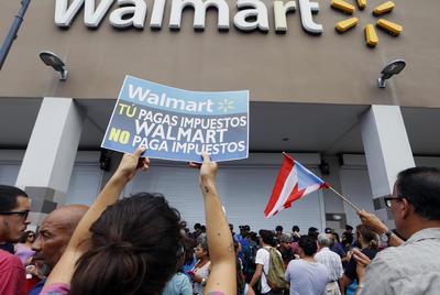 SAN JUAN (PUERTO RICO).- Manifestantes protestan en una tienda de Walmart, en San Juan (Puerto Rico). Decenas de personas protestaron hoy en San Juan contra la política laboral de la compañía estadounidense Walmart, lo que obligó a cerrar el local frente al cual se realizó la manifestación y a pedir intervención policial. EFE/Thais Llorca