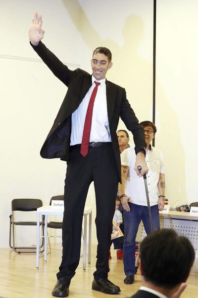 """SEÚL (COREA DEL SUR).- El hombre más alto del mundo, reconocido por el """"Guinness de los récords"""", el turco Sultan Kösen, de 2,51 metros de altura, saluda durante una rueda de prensa con motivo de la visita del Gran Circo de Europa, en Seúl, Corea del Sur. EFE"""