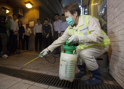 HONG KONG (CHINA).- Una mujer fumiga las alcantarillas en el distrito central de Hong Kong (China). Este año se han registrado tres casos de dengue y uno del virus zika en Hong Kong. EFE