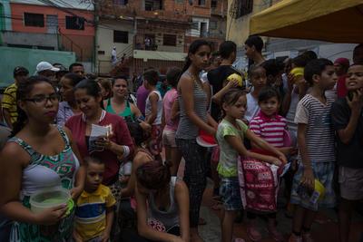 """CARACAS (VENEZUELA).- Habitantes esperan para recibir porciones de un sancocho, en la ciudad de Caracas (Venezuela). En el barrio la Unión, ubicado en la favela más grande de América Latina asentada en el este de Caracas, se preparó hoy un gran """"sancocho"""" como se le conoce en Venezuela a la sopa cocinada con varios tipos de verduras y carnes, para alimentar a los vecinos, muchos de ellos con varios días sin comer. EFE"""
