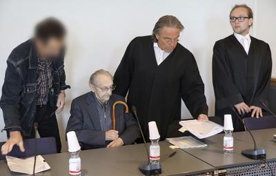 NEUBRANDENBURG (ALEMANIA).- Un exenfermero de las SS en el campo de exterminio de Auschwitz, el acusado Hubert Z. (2i), espera junto a sus abogados (d) en una sala de la Audiencia Provincial de Neubrandenburg, al este de Alemania. El juicio contra el acusado de 95 años ha sido pospuesto en tres ocasiones por motivos de salud del acusado. El proceso empezó finalmente hoy con asistencia en silla de ruedas del anciano, al que la fiscalía acusa de complicidad en el asesinato de al menos 3.681 personas en las instalaciones del campo en el que sirvió de enfermero durante un mes en el año 1944. EFE