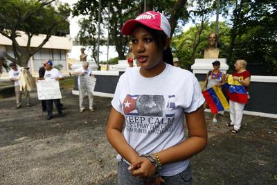 """SAN JUAN (PUERTO RICO).- Alicia Fariñas (c), hija de Guillermo Fariñas, el pasado viernes 9 de septiembre, junto a un grupo de disidentes cubanos y venezolanos, manifestándose en San Juan (Puerto Rico) en apoyo a su padre, en huelga de hambre desde hacía 51 días. Fariñas, dijo estar """"muy contenta"""" tras recibir la noticia de que su padre acabó la huelga de hambre y sed. La joven de 21 años explicó que primero recibió una llamada de su mamá y luego de su abuela, para anunciarle la decisión de su padre aunque, por el momento, desconoce los motivos por los cuales el opositor optó por ponerle fin a su protesta. """"Me dijeron que está muy débil y que no podía hablar"""", explicó Alicia, quien detalló que su padre """"tiene muy baja la hemoglobina"""". EFE"""