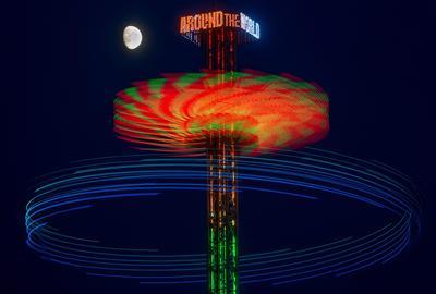 """FRÁNCFORT (ALEMANIA).- Fotografía de amplia exposición que muestra la luna creciente sobre la atracción """"Alrededor del mundo"""", en el parque Dippemess de Fráncfort (Alemania). EFE"""