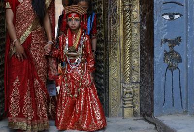 """KATMANDÚ (NEPAL).- Una niña nepalí vestida con un traje tradicional asiste a la ceremonia de culto Kumari Puja, en la que se adora a """"Kumari"""", una niña considerada una diosa viviente, en Katmandú, Nepal. Más de un centenar de niñas menores de 9 años de todo el país acudieron a esta ceremonia, que busca la protección del maligno y proporciona buena suerte en el futuro. El evento fue organizado por la Federación Mundial de la Juventud Hindú. EFE"""