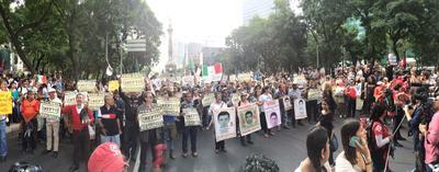 Madres de los 43 normalistas marcharon con las imágenes de sus hijos alrededor de su cuello.