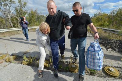 Schastye (Ucrania ).- Las autoridades ucranianas ayudar a Vladimir Zhemchugov (C), un prisionero de guerra ucranianos para cruzar una línea de minas, durante un intercambio de prisioneros cerca de la ciudad de Schastye, región de Lugansk, Ucrania. Un ex militar de Ucrania y un ex representante misión de la ONU fueron liberados por los rebeldes pro-rusos, mientras que cuatro ex rebeldes pro-rusos fueron puestos en libertad por Ucrania al mismo tiempo. EFE