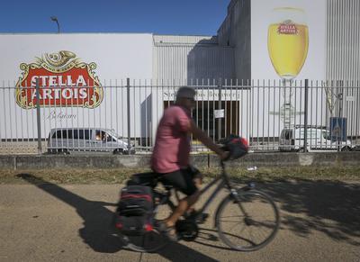 LOVAINA (BÉLGICA).- Un ciclista pasa junto al logo de la cerveza del primer grupo cervecero mundial AB InBev, Stella Artois, en sus oficinas de Lovaina, Bélgica. La cervecera belga AB InBev anunció un acuerdo de fusión multimillonario con la británica SABMiller. El mayor grupo cervecero mundial produce marcas como Corona, Budweiser o Stella Artois, mientras que la británica SABMiller produce la cerveza Foster, entre otras. EFE