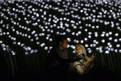 SERDANG (MALASIA).- Una pareja hace una foto durante el evento 'The Nightscape of Light Sensation ? Love Series' (El Paisaje Nocturno de la Sensación de la Luz - Series de Amor) en Serdang, en las afueras de Kuala Lumpur, Malasia. El evento se forma por un decorado de un total de 30.000 luces de led y rosas blancas para promocionar al país a nivel internacional. EFE