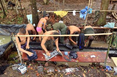 EL DIAMANTE (COLOMBIA).- Guerrilleros del Bloque Sur de las FARC se bañan luego de un día de trabajo durante la Décima Conferencia Nacional Guerrillera, en El Diamante (Colombia). EFE