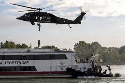 """VIENA (AUSTRIA).- Fuerzas especiales de las Fuerzas Armadas de Austria asaltan una embarcación desde un helicóptero Blackhawk Utility S-70 y desde una lancha motora, durante una maniobra militar con motivo de la operación aeronaval de la Unión Europea en el Mediterráneo, operación """"Sophia"""", en el río Danubio en Viena, Austria. Según anunció el portavoz de las Fuerzas Armadas de Austria, cerca de 30 soldados serán enviados para combatir en la operación """"Sophia"""" en 2017. La operación cuenta con 24 países participantes y tiene como objetivo luchar contra las redes de tráfico de personas, prevenir flujos de migración irregular y evitar que muera más gente en el mar. EFE"""