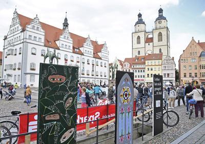 WITTENBERG (ALEMANIA).- Vista general de las 95 tesis en la plaza Marktplatz en Wittenberg, Alemania. La galería que representa las 95 tesis de Martín Lutero está pintada por personas de todas las edades y forma parte de las celebraciones del 500º aniversario de Martín Lutero (1483-1546) desde que colgó las 95 tesis en la puerta de la iglesia All Saints' en Wittenberg. EFE