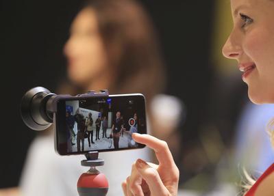 """COLONIA (ALEMANIA).- Una mujer prueba un objetivo fotográfico para teléfonos inteligentes de Zeiss en la Feria de la Fotografía """"Photokina"""" en Colonia (Alemania). EFE"""