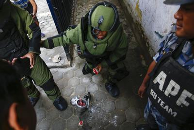 KATMANDÚ (NEPAL).- Un experto en explosivos manipula una olla a presión, utilizada como bomba casera, mientras intenta desarmarla cerca del colegio Kanchanjangha en Katmandú (Nepal). Un total de siete ollas a presión han sido localizadas en varios colegios de la capital nepalí y han sido desactivadas con éxito por la policía y el ejército. EFE