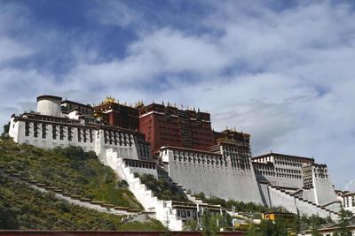 """LHASA (CHINA).- Fachada principal de el Potala, el histórico palacio de los lamas en Lhasa, la capital tibetana, que mantiene su magia entre la explosión turística y urbanística de la ciudad, que ha causado un importante incremento de las visitas. El edificio, cuyos orígenes se remontan al siglo VII aunque la mayoría de la construcción actual data del siglo XVII, preside Lhasa desde la llamada """"colina roja"""" y alcanza más de 300 metros de altura sobre el valle del río del mismo nombre. La construcción tiene 13 pisos y mide unos 400 metros de este a oeste, por 350 de norte a sur, con unas mil salas que totalizan 400.000 metros cuadrados, de los que ahora se usan unos 130.000. EFE"""