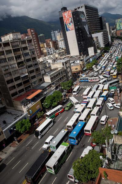 CARACAS (VENEZUELA).- Fotografía donde se ve una calle bloqueada por autobuses de servicio público durante una protesta de conductores del servicio, en las inmediaciones del Ministerio de Transporte en Caracas (Venezuela). La protesta es para exigir un aumento del costo del pasaje y contra la escasez de repuestos. EFE