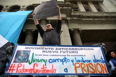 CIUDAD DE GUATEMALA (GUATEMALA).- Manifestantes protestan contra el presidente guatemalteco, Jimmy Morales, en Ciudad de Guatemala (Guatemala). Medio centenar de guatemaltecos manifestaron hoy descontento contra el presidente Jimmy Morales, cuyo hijo y un hermano supuestamente están involucrados en un caso de corrupción. Con banderas, cárteles y tambores, los manifestantes llegaron a las afueras del Palacio Nacional de la Cultura, en el centro histórico de la capital, donde lanzaron consignas contra el mandatario y su Gobierno. EFE