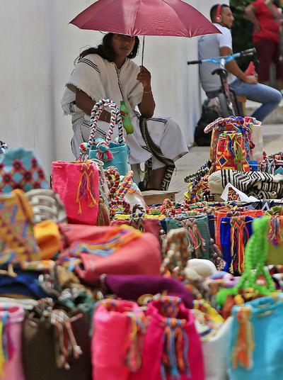 """CARTAGENA (COLOMBIA). Un indígena arhuaco vende artesanías, en Cartagena (Colombia). El acuerdo de paz, negociado durante casi cuatro años en La Habana, será firmado el lunes por el presidente de Colombia, Juan Manuel Santos, y por el jefe máximo de las FARC, Rodrigo Londoño Echeverri, alias """"Timochenko"""", en un acto en Cartagena al que asistirán unos 2.500 invitados. EFE"""