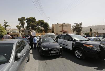 Amman (Jordania).- policías jordanos y personas de pie en frente del Hospital de Luzmila en Amman, donde fue llevado el cuerpo del escritor jordano Nahed Hattar. Hattar, que provocó controversia por publicar una caricatura considerado ofensivo al Islam, fue muerto a tiros el 25 de septiembre frente a un tribunal en la capital jordana, Amman. EFE