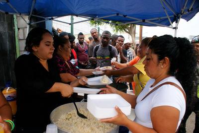 """TIJUANA (MÉXICO).- Fotografía de ciudadanos haitianos recibiendo comida que les ofrecen mexicanos en la fronteriza ciudad mexicana de Tijuana en espera de cruzar hacia territorio estadounidense. Un """"embudo"""", así es descrita estos días la ciudad mexicana de Tijuana, en la que cientos de migrantes haitianos permanecen varados a la espera de pasar la frontera hacia EE.UU. para buscar una nueva vida, una vez acabadas las oportunidades en la tierra que les dio acogida, Brasil. EFE"""