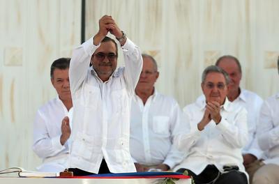 El líder de las FARC levantó los brazos y recibió una salva de aplausos mientras alzaba las manos cruzadas a modo de abrazo.