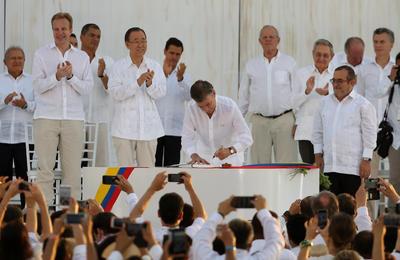 """El presidente de Colombia, Juan Manuel Santos, y el líder de las FARC, Rodrigo Londoño Echeverri, alias """"Timochenko"""", firmaron un acuerdo de paz."""