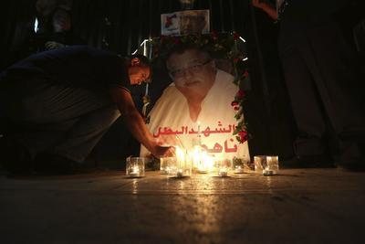 AMMÁN (JORDANIA).- Un hombre deja una vela en la imagen del fallecido escritor cristiano Nahed Hattar durante una manifestación contra el gobierno con flores y velas delante del Tribunal jordano en Ammán (Jordania). Los manifestantes exigen la dimisión del primer ministro, Hani Mulki, tras el asesinato del escritor Hattar a disparos cuando acudía ayer a un tribunal de Ammán para ser juzgado por la difusión de una caricatura en su página de Facebook considerada blasfema para el islam. EFE
