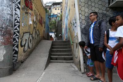 """RÍO DE JANEIRO (BRASIL).- Habitantes de la favela Santo Amaro con temor de subir a su hogar en Río de Janeiro (Brasil). Una banda de narcotraficantes aplicó hoy un toque de queda en Catete, un tradicional barrio de clase media próximo al centro de Río de Janeiro, en un alarde de su poder y como respuesta a la muerte de """"Fat Family"""", uno de los capos más buscados de Brasil, a manos de la Policía. Todos los establecimientos comerciales a lo largo de unos cinco kilómetros bajaron sus pesadas verjas metálicas al unísono a mediodía, cuando dio la orden un grupo de integrantes del Comando Vermelho, la mayor banda armada de Brasil. EFE"""
