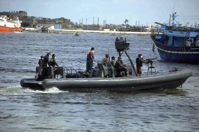 ROSETTA (EGIPTO).- Un barco RHIB militar devuelve los cadáveres de las personas desaparecidas a sus familiares, que se reúnen junto a militares en el puerto de Rosetta, a 250 kilómetros del norte de El Cairo, Egipto. El Gobierno egipcio prometió intensificar la vigilancia en los puertos y las costas mediterráneas del país para poner fin a la emigración ilegal, después de que 164 personas perdieran la vida en el naufragio de un barco el pasado miércoles en el Mediterráneo. EFE