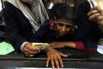 SANÁ (YEMEN).- Un joven dona dinero con su familia para el Houthi rebels-held Central Bank en Saná (Yemen). De acuerdo con teportes de prensa el líder rebelde Houthi Abdul-Malik al-Houthi solicitó apoyo financiero a los ciudadanos de Yemen, después de que el gobierno yemení de respaldo saudí reubicara el Banco Central del rebel-held Saná a la ciudad portuaria de Adén, acusando a los Houthis de usar reservas del banco para financiar sus milicianos. EFE