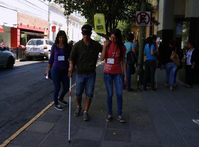 PAR10. ASUNCIÓN (PARAGUAY) 27/09/2016 - Un hombre se presta como voluntario para caminar con los ojos vendados y con la ayuda de un bastón hoy, martes 27 de septiembre de 2016, en Asunción (Paraguay). Paraguay celebró el Día Mundial del Turismo con actividades que instaron a los transeúntes a vivir el turismo desde una silla de ruedas, o con los ojos vendados y un bastón, con el fin de sensibilizar sobre la accesibilidad de los lugares turísticos para personas con discapacidad. EFE/Alberto Peña