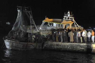 ROSETTA (EGIPTO).- Fotografía que muestra a varias personas ayer en un muelle mientras el barco que naufragó con cientos de inmigrantes a bordo, es remolcado al puerto de la ciudad de Rosetta, a unos 250 km al norte del Cairo, Egipto. En el interior del barco fueron hallados 33 cadáveres, por lo que la cifra de muertos en el naufragio asciende a 204, hasta el momento. Además, 160 personas salvaron la vida de los cientos que se echaron a la mar, cuyo número exacto se desconoce pero que las autoridades y medios locales situaron entre 400 y 600, la mayoría de ellos egipcios y emigrantes de diferentes nacionalidades africanas. Se cree que el barco se dirigía a Italia, hacia donde intentan emigrar de forma irregular cada año miles de egipcios, cifras que han aumentado en los últimos meses. EFE