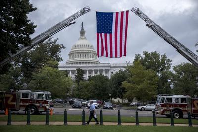 """WASHINGTON, DC (EEUU).- Vista de una bandera estadounidense desplegada desde dos camiones de bomberos durante la votación del Senado en Washington, DC, votó hoy a favor de anular el veto del presidente, Barack Obama, sobre una ley que permitiría a los estadounidenses demandar al Gobierno de Arabia Saudí por su supuesto papel en los atentados del 11 de septiembre de 2001 (11S). Con 348 votos a favor y 77 en contra, los legisladores de la Cámara de Representantes se unieron a sus compañeros del Senado, que ya hoy se opusieron al veto para, por primera vez en ocho años del mandato de Obama, invalidar la negativa presidencial a una ley. Con esta invalidación del veto, entra en vigor automáticamente la conocida como """"Ley de Justicia contra Promotores del Terrorismo"""", que permitiría a los familiares de víctimas del 11S interponer demandas en cortes de EEUU contra el Gobierno saudí por su supuesto apoyo a los terroristas que perpetraron los atentados. EFE"""