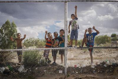 """ALBURQUERQUE (NM, EEUU).- Fotografía que muestra un grupo de niños mexicanos que observan la construcción de un muro de acero en la localidad de Sunland Park, en Nuevo México (México). Los casi dos kilómetros del muro de acero reforzado que levanta Estados Unidos en la localidad fronteriza de Sunland Park, en Nuevo México, suponen para muchos vecinos una pérdida de dinero y una """"humillación"""". En esta ciudad vecina de El Paso (Texas) ya se ven los primeros 50 metros de acero que la dividen de Anapra, comunidad de Chihuahua (México), en una construcción que se inició en plena polémica por la propuesta del candidato republicano, Donald Trump, de levantar un muro en toda la frontera sur. EFE"""