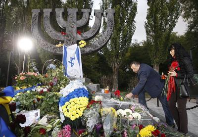 KIEV (UCRANIA).- Ucranianos dejan ofrendas florales, banderas de Israel y velas en el monumento Minora, durante una ceremonia de duelo cerca del barranco Babiy Yar en Kiev (Ucrania). Los ucranianos conmemoran el 75 aniversario de la matanza nazi en el barranco Babiy Yar, donde unos 34.000 judíos fueron asesinados durante dos días de septiembre en 1941. En total, más de 100.000 personas perdieron la vida en Babiy Yar entre 1941 y 1943 durante la Segunda Guerra Mundial. EFE
