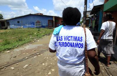 APARTADÓ (COLOMBIA).- Fotografía de la señora Alba Rosa Gómez (i) en una calle del barrio La Chinita en Apartadó (Colombia). Una lámina plástica pegada en una pared con los nombres de las 35 personas asesinadas por las FARC la noche del 23 de enero de 1994 es el único recuerdo visible de una de las peores matanzas perpetradas por esa guerrilla, la de La Chinita, una calle de la ciudad colombiana de Apartadó. Pero en La Chinita, un barrio de gente pobre en el que las calles son de tierra y en época de lluvias un lodazal, todos recuerdan lo que pasó aquella noche, bien sea porque lo vivieron o porque, en el caso de los más jóvenes, han escuchado los relatos de los mayores. EFE