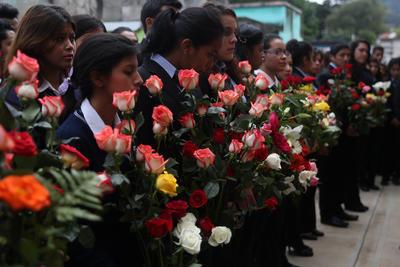 SANTA CATARINA PINULA (GUATEMALA).- Fotografía de estudiantes y familiares en una ceremonia frente las tumbas de sus compañeros y parientes fallecidos durante el derrumbe de El Cambray II, un año después del desastre, en Santa Catarina Pinula (Guatemala). El Cambray II, que es ahora una zona inhabitable, aledaña a la capital de Guatemala, es el barrio que quedó arrasado por un deslizamiento de tierra que dejó 280 muertos y 70 desaparecidos. EFE