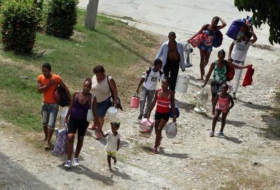 """GUANTÁNAMO (CUBA).- Varias personas evacuadas arriban a una escuela convertida en albergue, en la ciudad de Guantánamo (Cuba), ante la proximidad del huracán Matthew. Seis provincias de Cuba se encuentran bajo """"alarma ciclónica"""" a la espera del potencial impacto del huracán Matthew, que previsiblemente tocará tierra por Guantánamo, en el extremo más oriental de la isla, informó hoy el Estado Mayor Nacional de la Defensa Civil de la isla. EFE"""
