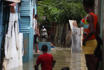 SANTO DOMINGO (REPÚBLICA DOMINICANA).- Dominicanos afectados por inundaciones hoy, martes 4 de octubre de 2016, durante el paso del huracán Matthew en Santo Domingo (República Dominicana). En la República Dominicana, tres menores y un adulto murieron por derrumbes provocados por las intensas lluvias del huracán, que provocó el desplazamiento de 18.545 personas en todo el país, informó hoy el Centro de Operaciones de Emergencias (COE). EFE