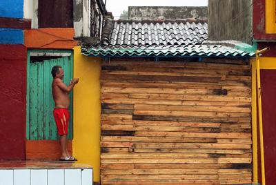 """BARACOA (CUBA).- Un hombre asegura un portón en su vivienda, en la ciudad de Baracoa, en Guantánamo (Cuba). El """"extremadamente peligroso"""" huracán de categoría 4 Matthew, que presenta vientos máximos sostenidos de 145 millas (230 km/h), descargará su furia sobre Cuba esta tarde, informó hoy el Centro Nacional de Huracanes (NHC) de EE.UU. EFE"""