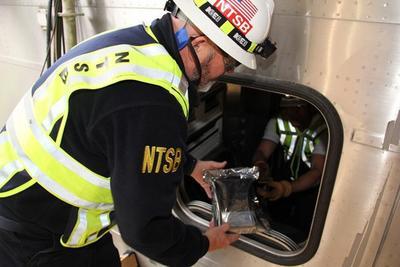 HOBOKEN (EE.UU.).- Fotografía cedida por la Junta de Seguridad de Transportación Nacional (NTSB), muestra a Michael Hiller (d), investigador de la NTSB, en la cabina de control del tren # 1614 NJ Transitís Pascack Valley Line, mientras entrega al investigador James Southworth, el registrador de eventos que será enviado a Washington, (Estados Unidos), desde Hoboken (Estados Unidos), donde se analizarán los datos capturados en los registradores como parte de la investigación NTSBís, para identificar la causa del accidente del tren que chocó contra la estación de Hoboken, hiriendo a 108 pasajeros y matando al menos a una persona que se encontraba en el andén de la estación de tren de Hoboken en Hoboken, Nueva Jersey, EE.UU., el 29 de Septiembre de 2016. EFE