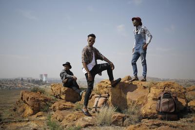 """SOWETO (SUDÁFRICA).- Fotografía que muestra a los jóvenes marcatendencias sudafricanos (izda-dcha) 2BA, Mphoza y Banzo posando en una colina cerca de sus hogares en Soweto, Sudáfrica. Los tres son peluqueros y junto con otro colega, Tumelo 'Zibstar' Zibi, han lanzado su propia tendencia en el modo de vestir combinando prendas compradas en tiendas de segunda mano y en establecimientos de bajo coste de centros comerciales. Todo ello para intentar inspirar al público para que vista con elegancia en cualquier ocasión. Además, para romper estereotipos de género, suelen lucir vestidos y faldas en combinación con chaquetas masculinas. Su objetivo no es llevar moda """"de marca"""", sino crear un estilo elegante, estiloso, único y diferente sin gastar mucho dinero. EFE"""