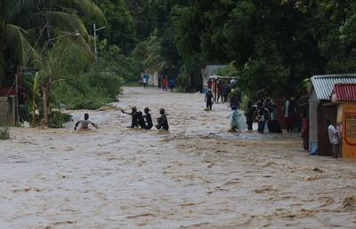LEOGANE (HAITI).- Personas intentan cruzar una calle inundada tras el paso del huracán Matthew, en Leogane (Haití). El poderoso huracán de categoría 4 Matthew continúa su ruta con vientos máximos de 140 millas por hora (220 km/h). La región sur de Haití sigue hoy incomunicada por los estragos causados por el poderoso huracán Matthew, que azotó el país este martes y causó al menos nueve muertos. EFE